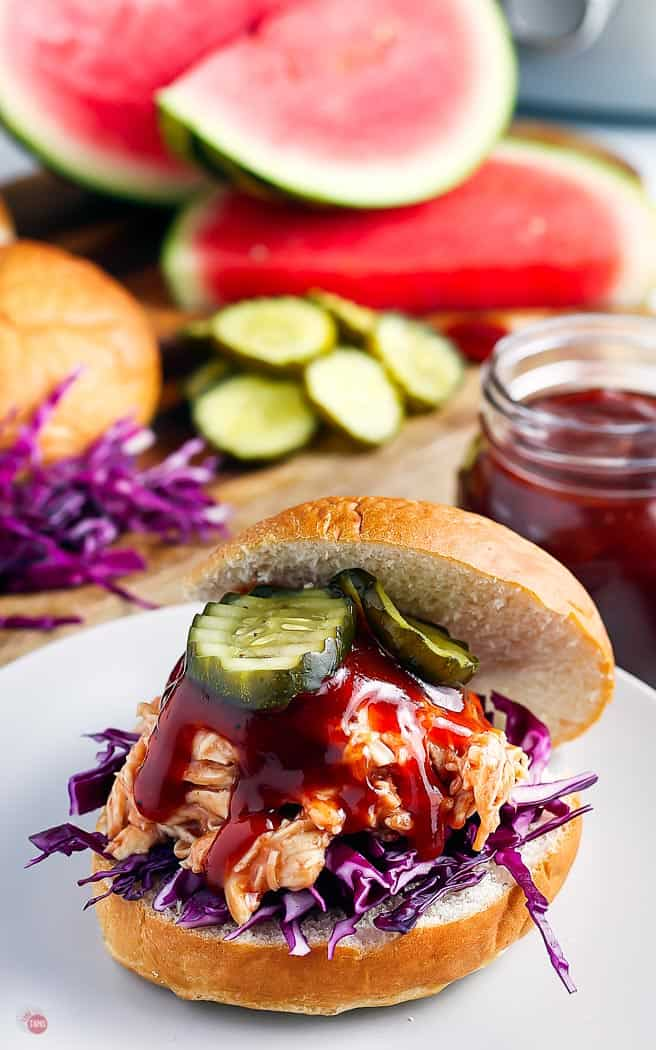 closeup of bbq chicken on a hamburger bun with pickles