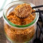 square photo of taco seasoning being scooped out of a clear jar