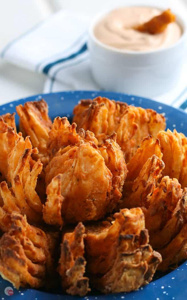 blooming onion in a blue enamel bowl