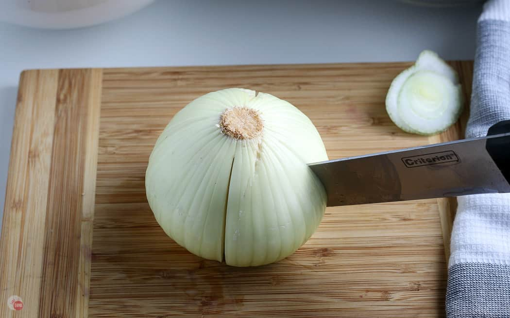 knife cutting down a whole onion