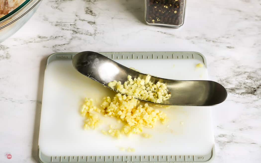 garlic minced on a white cutting board