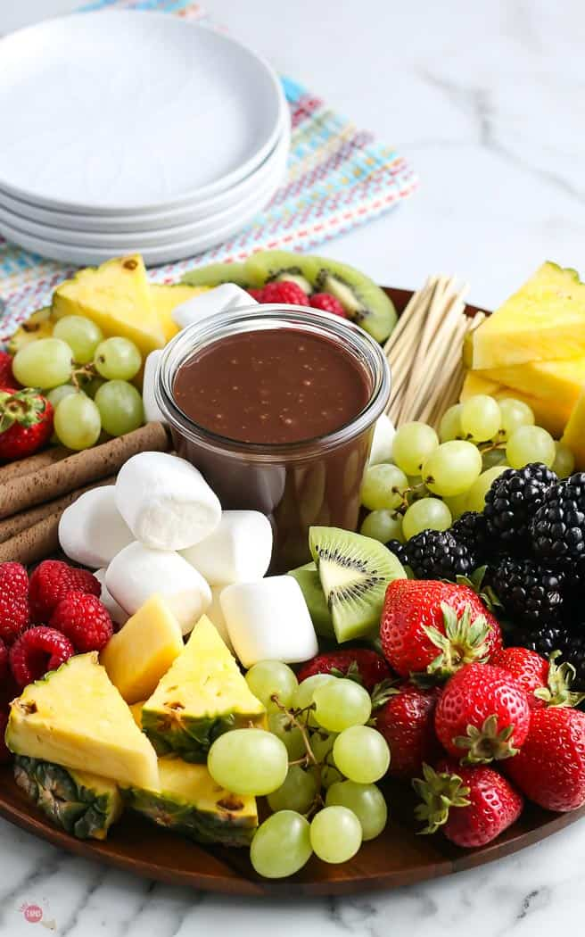 chopped fruit on a board with fudge sauce