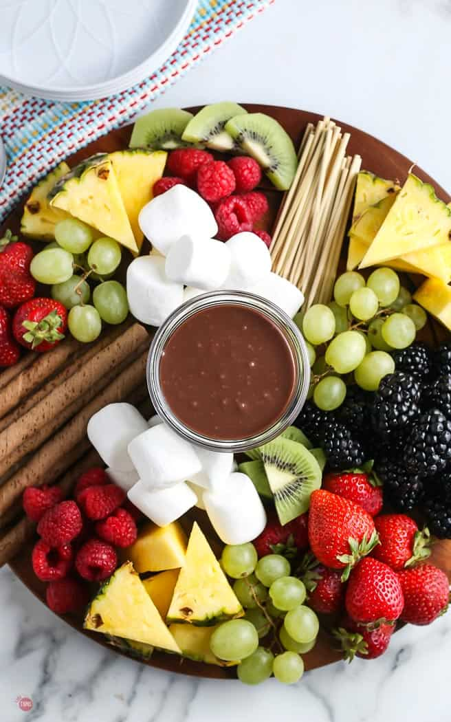 overhead picture of a wood board with chopped fruit and chocolate sauce