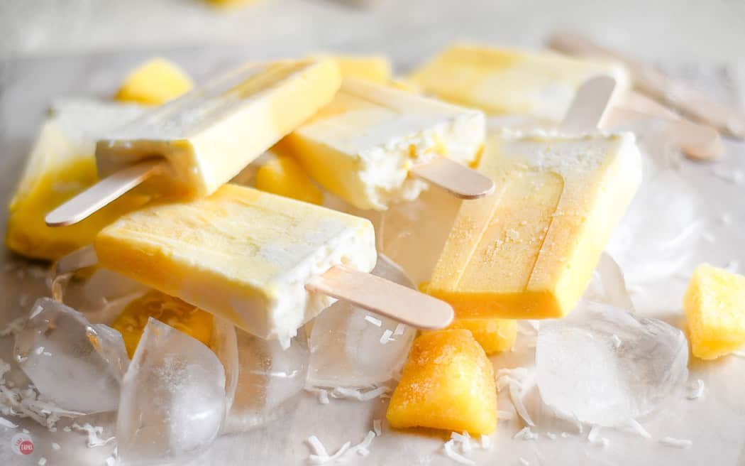side view of obmre colored popsicles on a bed of ice cubes