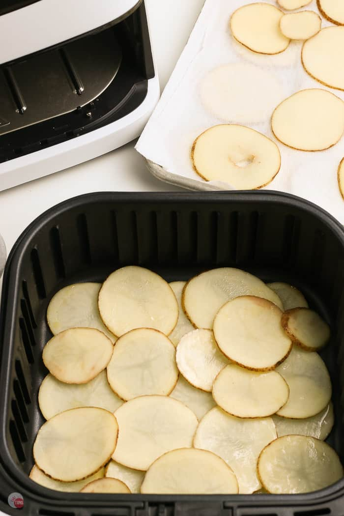 raw potato slices in an air fryer basket