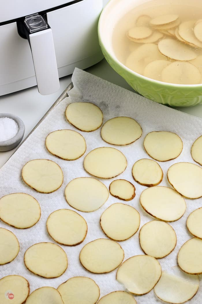 potato slices drying on paper towels
