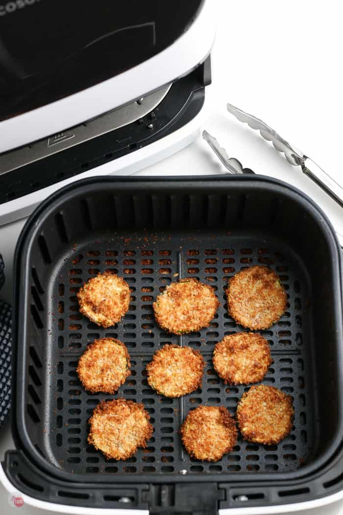 cooked breaded zucchini slices in air fryer basket