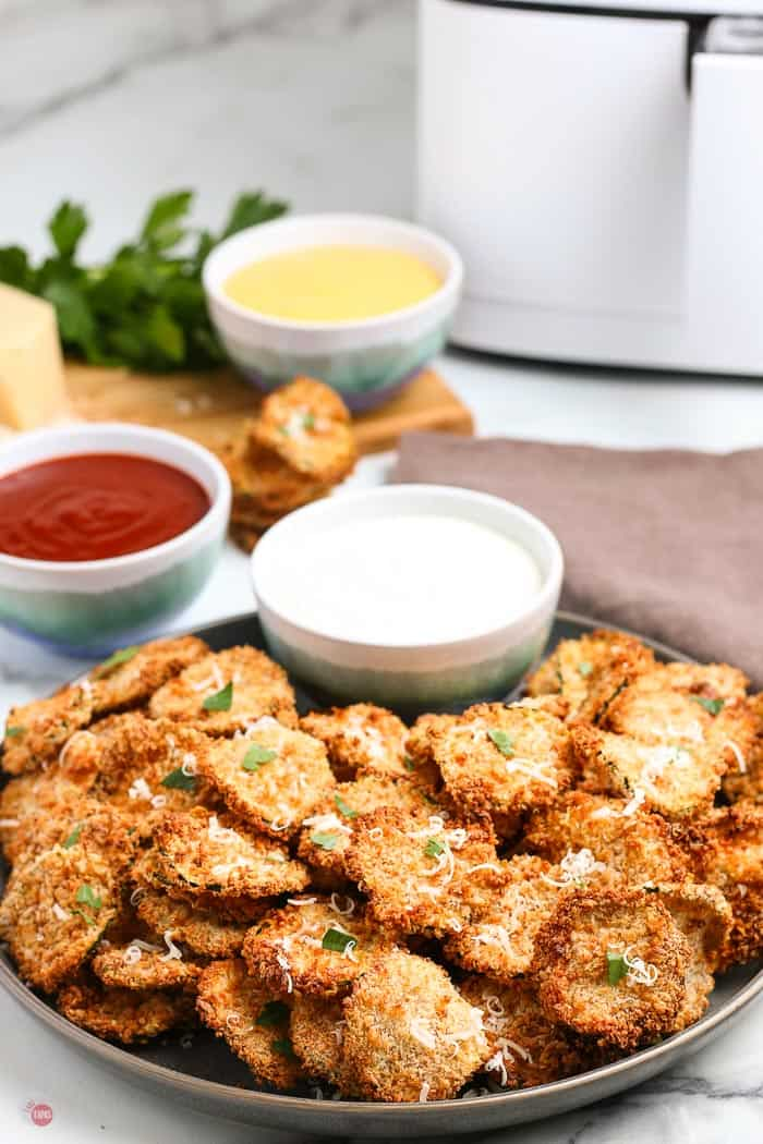 side view of air fried zucchini chips with dips