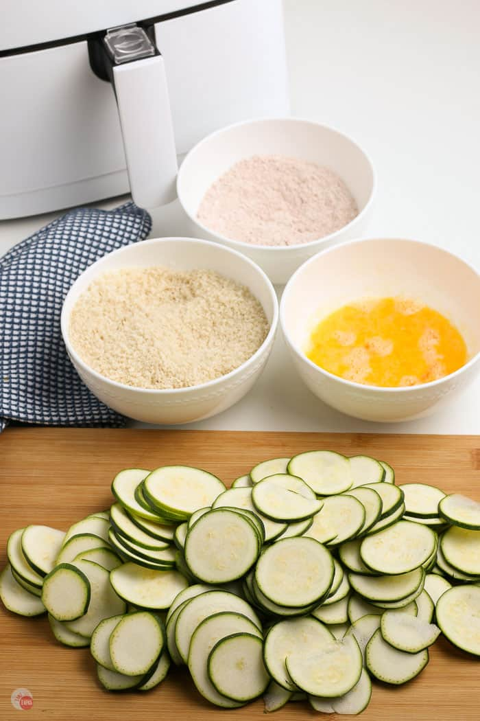 zucchini slices with three bowls of breading