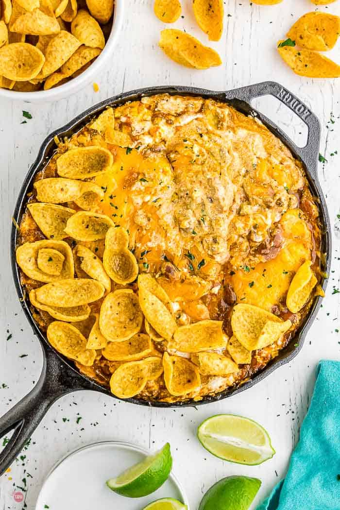 frito pie dip in a black skillet with limes