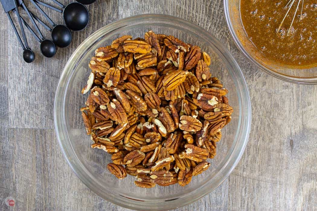 pecans in clear bowl with bowl of sauce and measuring spoons