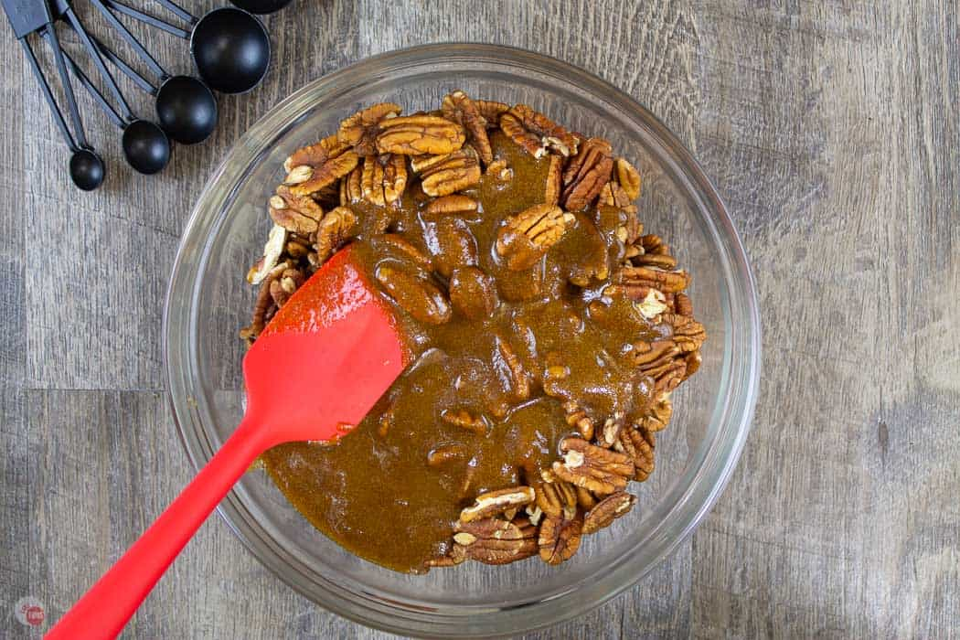 pecans and sauce in a bowl with a red spatula