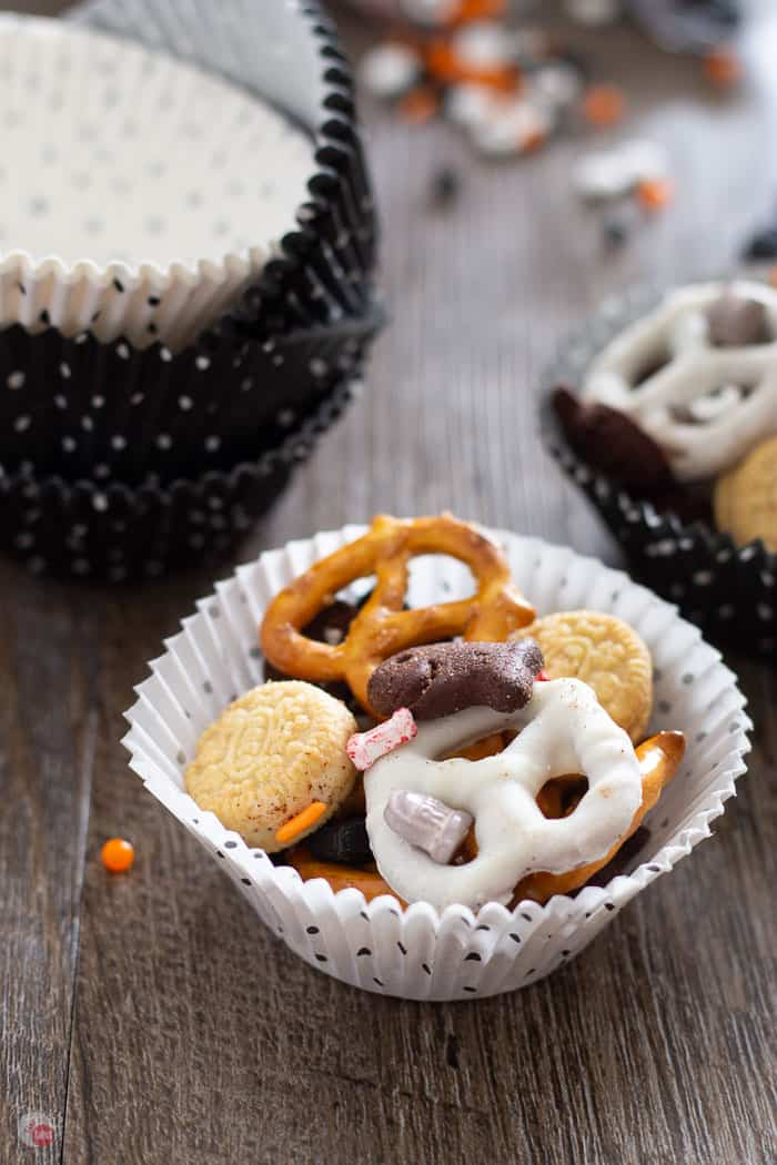 close up of halloween snack mix in a white muffin liner