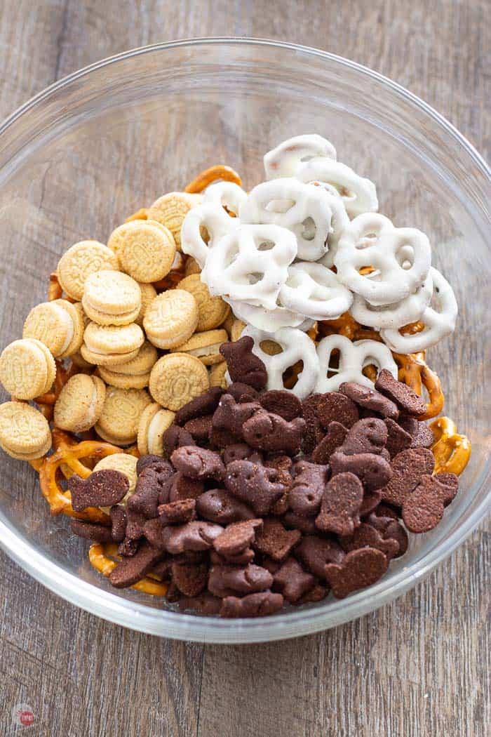 pretzels, mini oreo cookies, yogurt pretzels, chocolate cookies, in a clear bowl