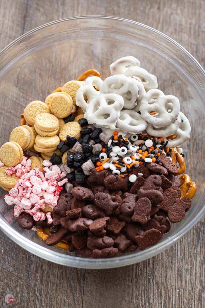 pretzels, mini oreo cookies, yogurt pretzels, chocolate cookies, and candies in a clear bowl