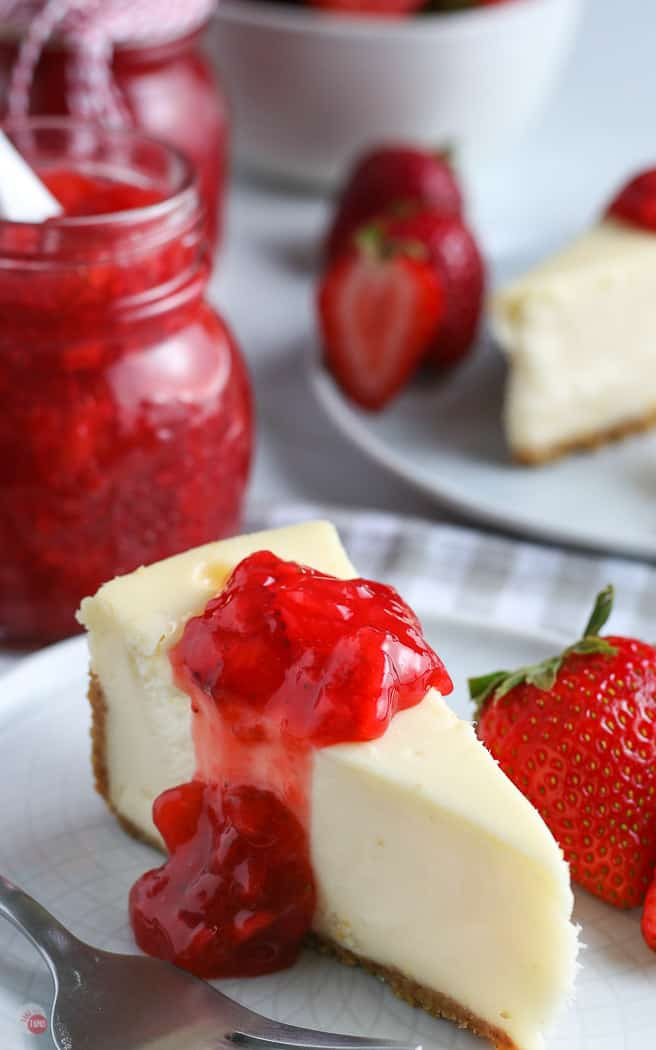 slice of cheesecake with strawberry sauce on a white plate