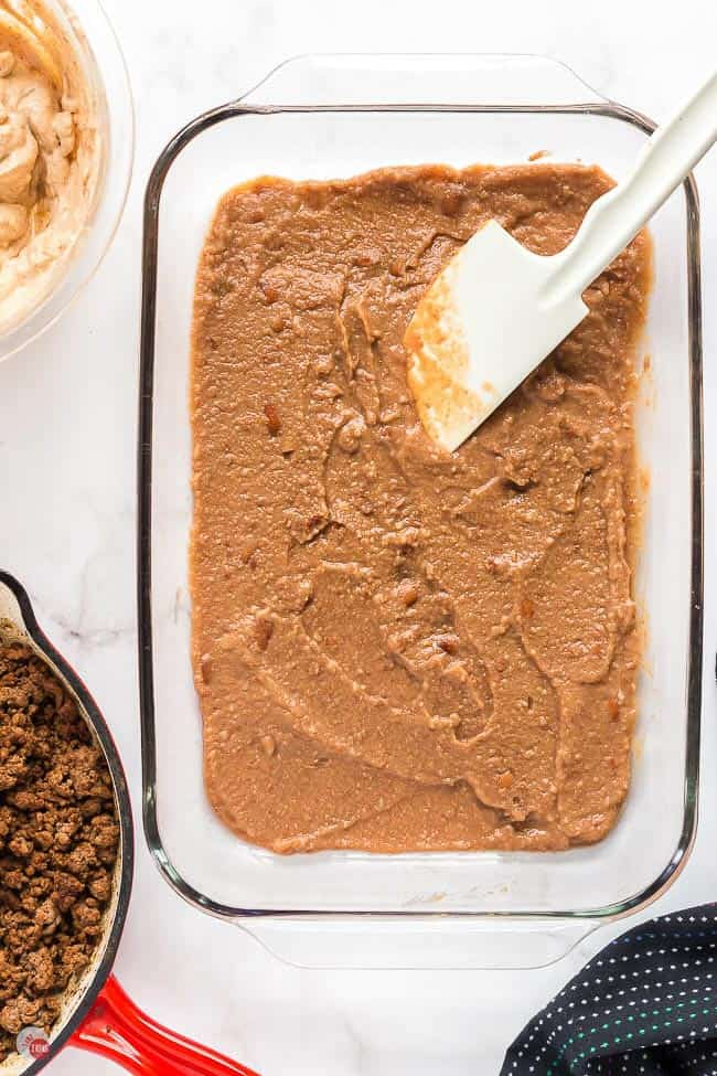 refried beans in a clear dish with spatula