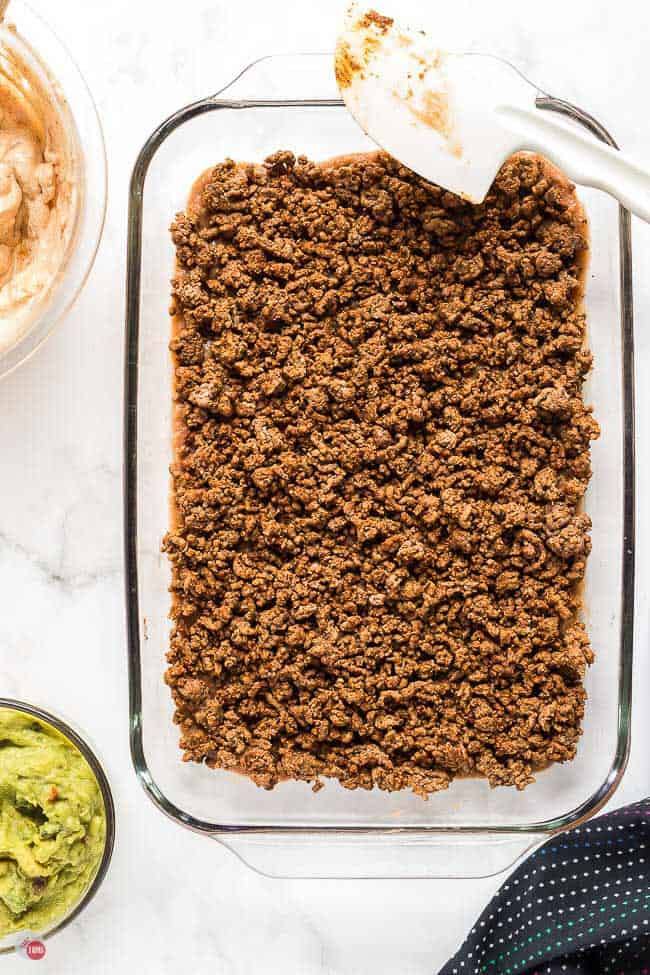 ground beef in a clear dish with spatula