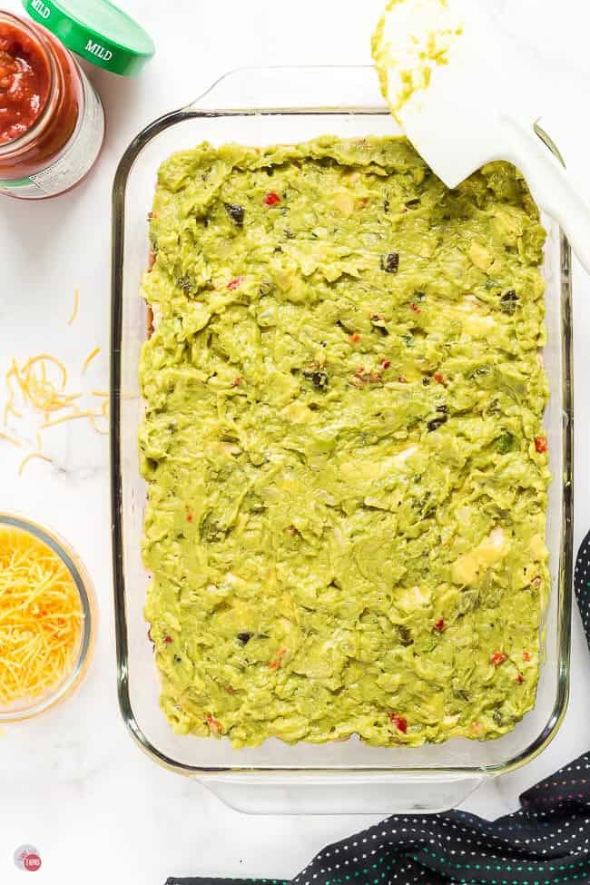 guacamole layered in a clear dish with spatula