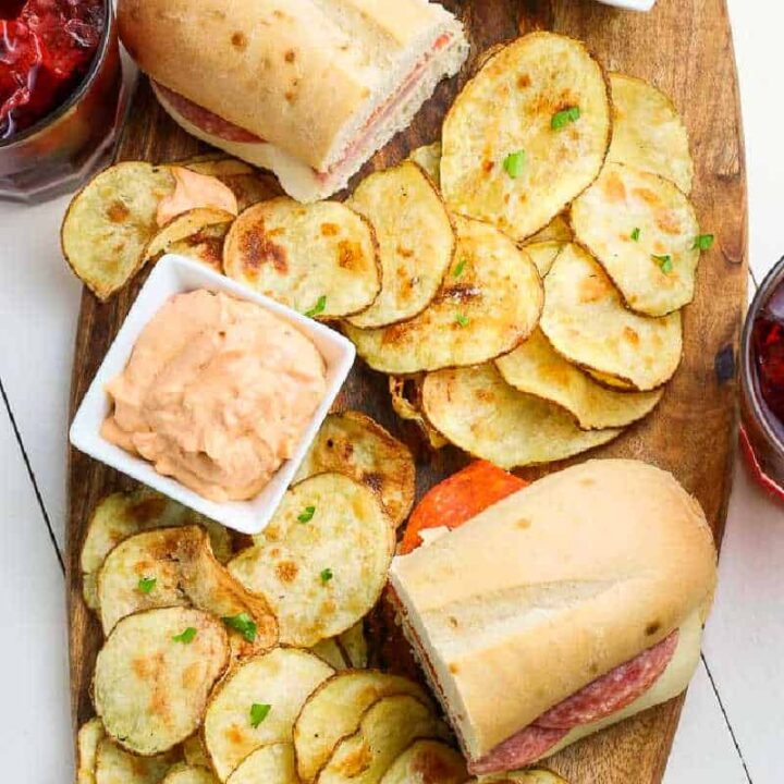 overhead picture of wood board with chips and sandwiches