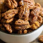square photo of candied pecans in a white bowl for recipe card