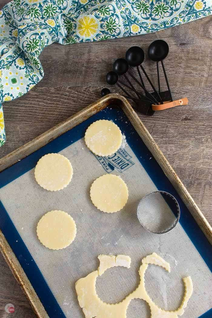 cookie dough cut into rounds on a cookie sheet