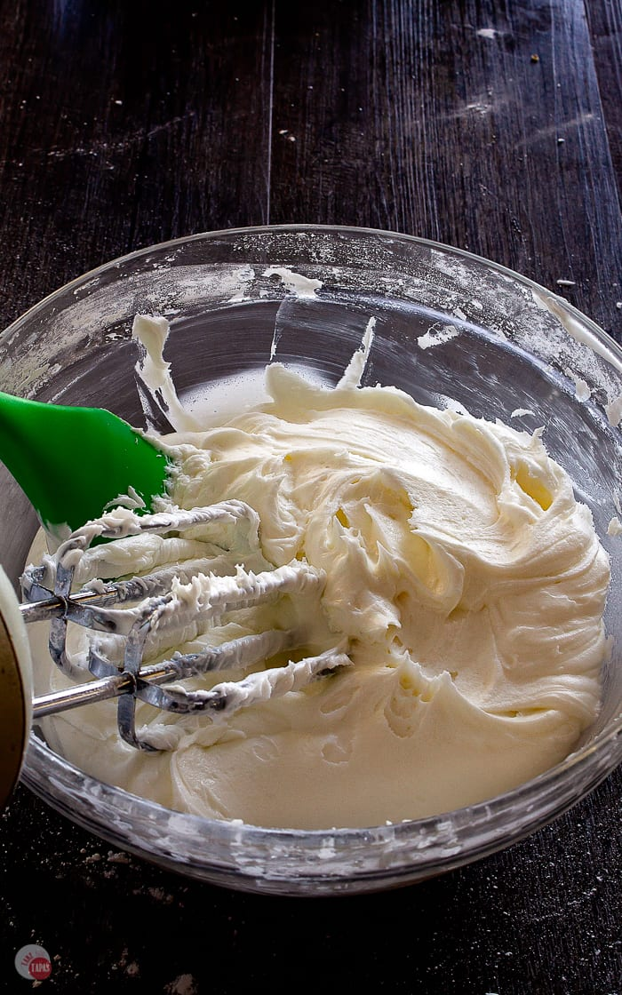 bowl of frosting with green spatula and beaters