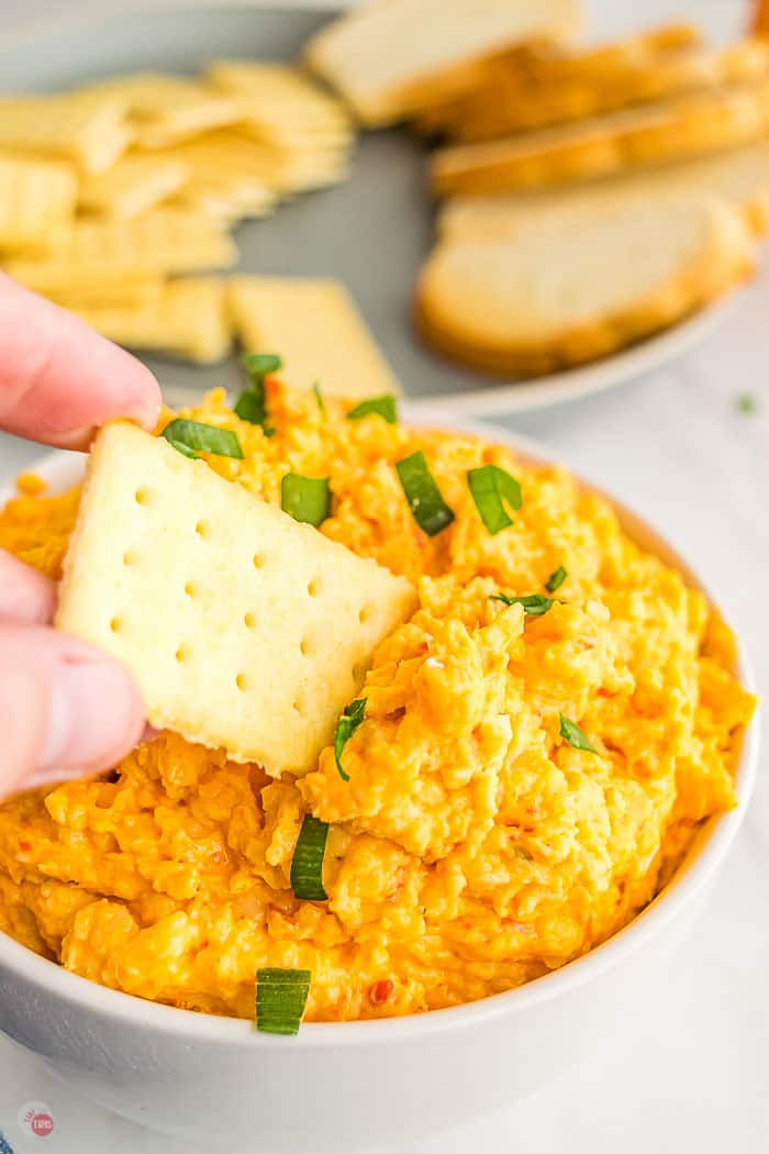 hand dipping a cracker into a bowl of pimento cheese spread