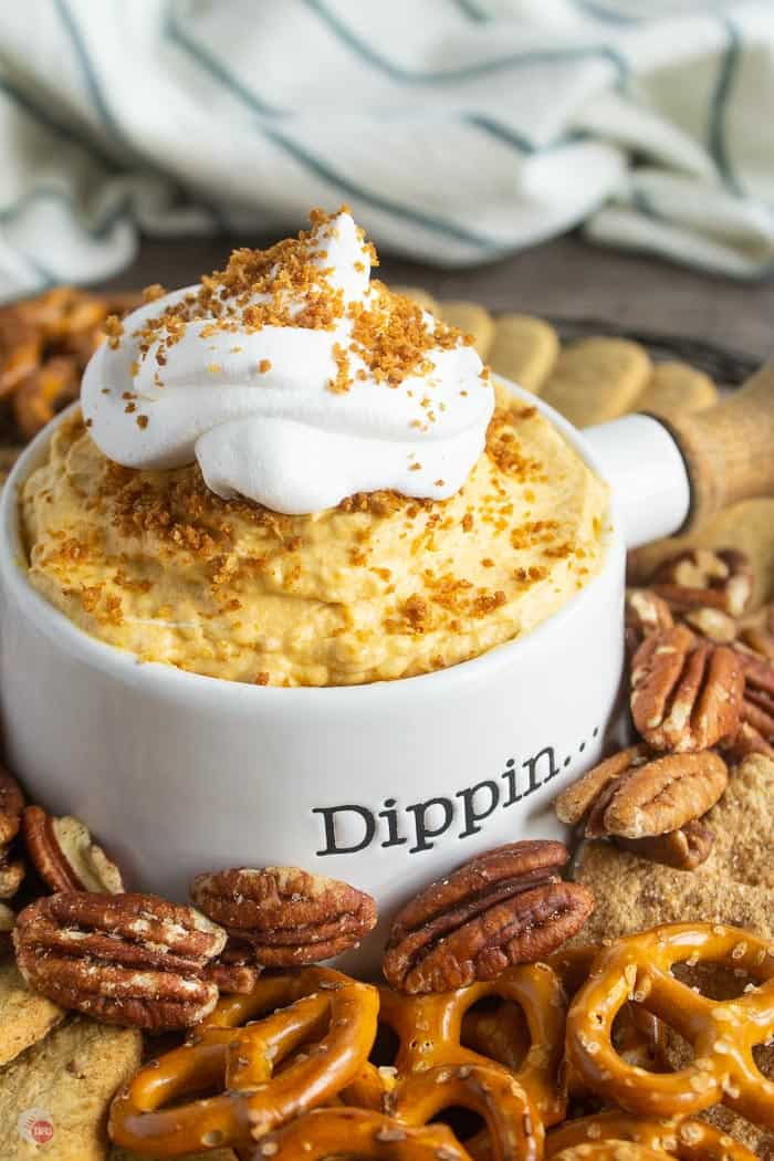 pumpkin dip in a white bowl surrounded by pretzels