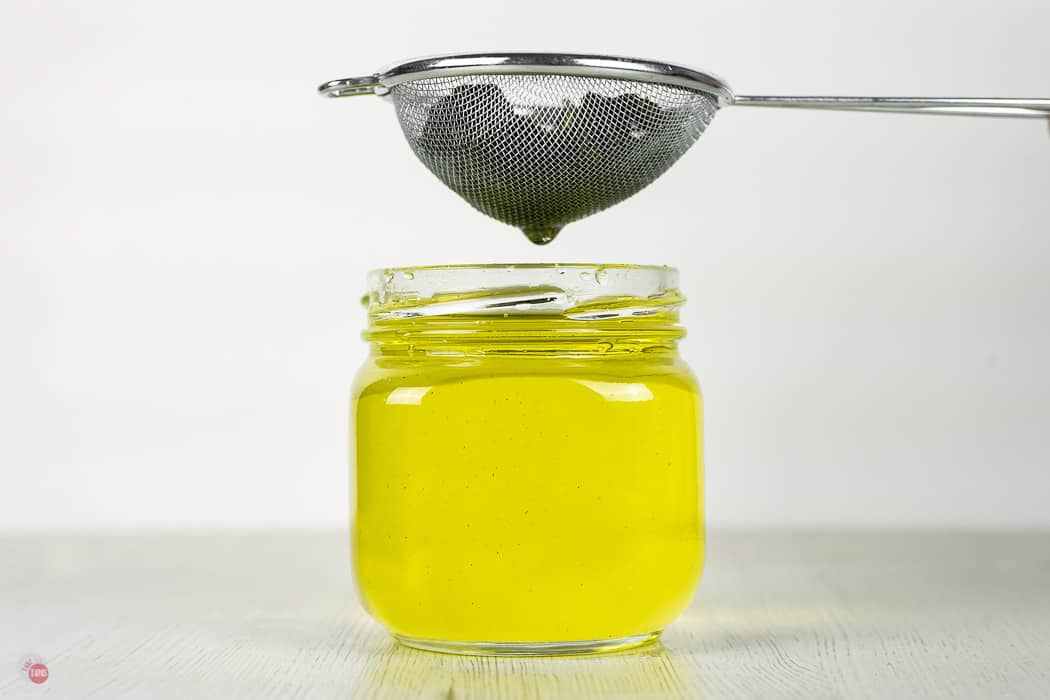 jar of yellow syrup with a sieve