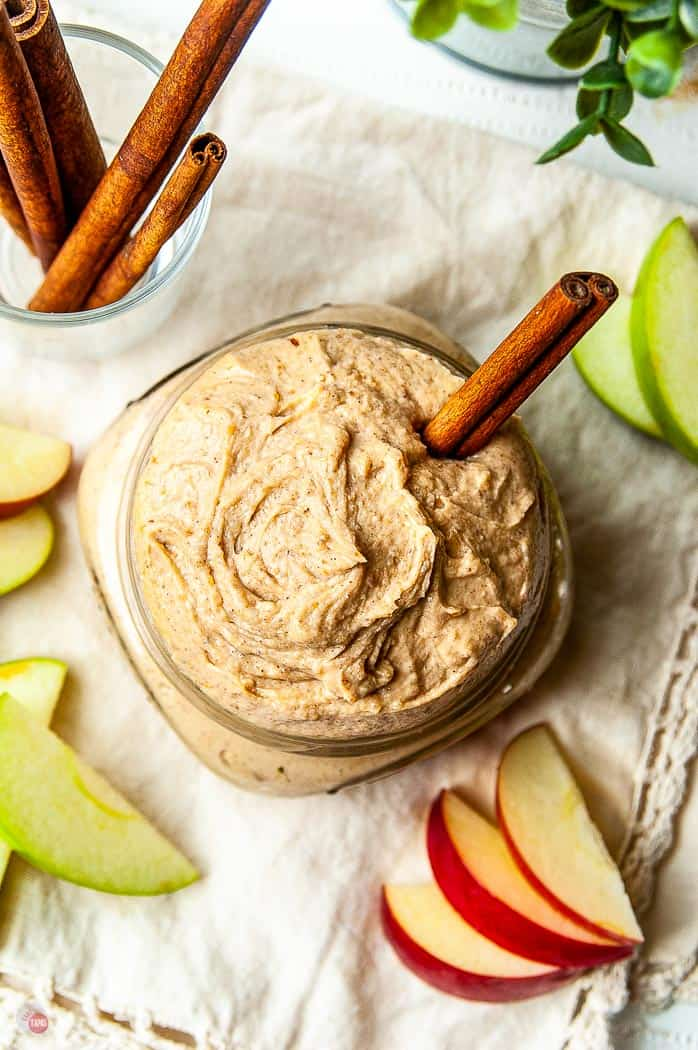overhead shot of dip with apple slices and a cinnamon stick