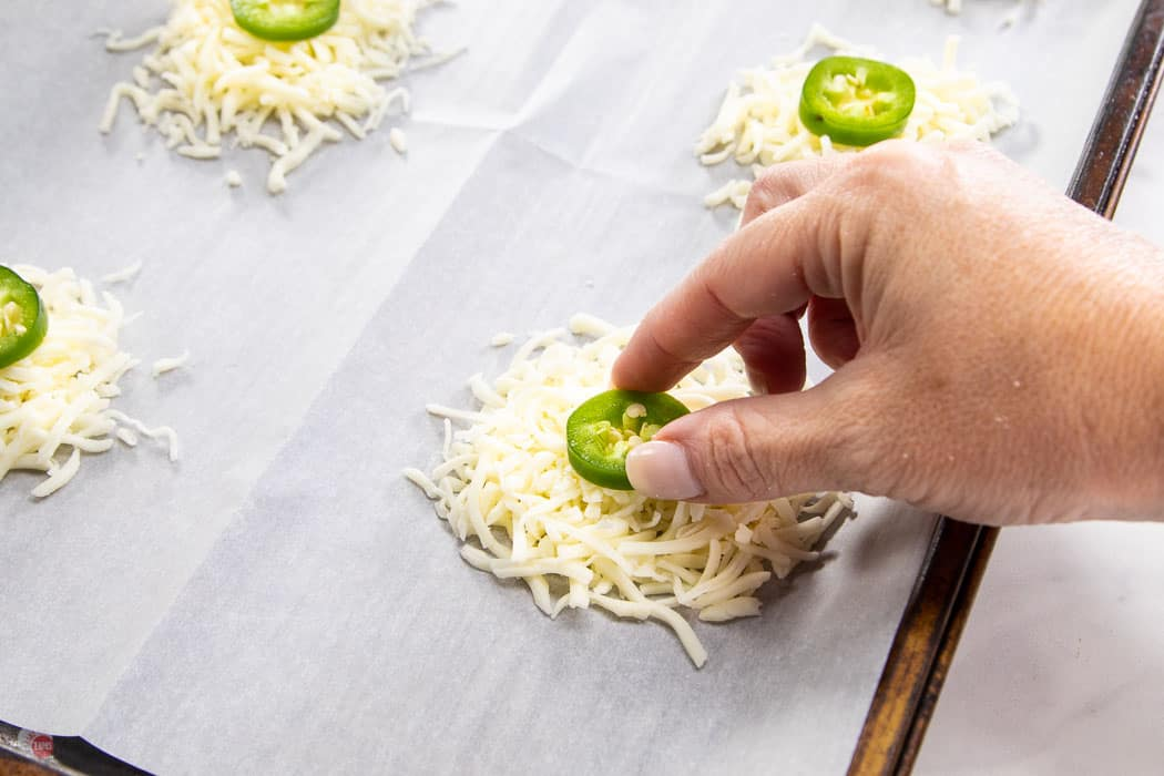 hand placing slice of jalapeno on cheese