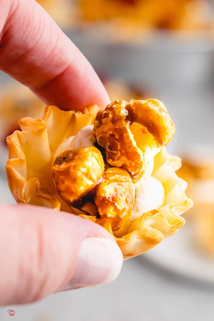single caramel corn phyllo cup in a hand