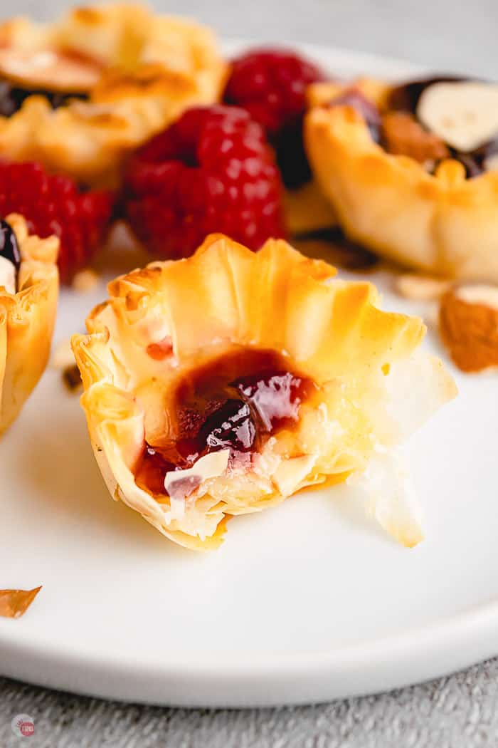 raspberry brie phyllo cup with bite removed on white plate