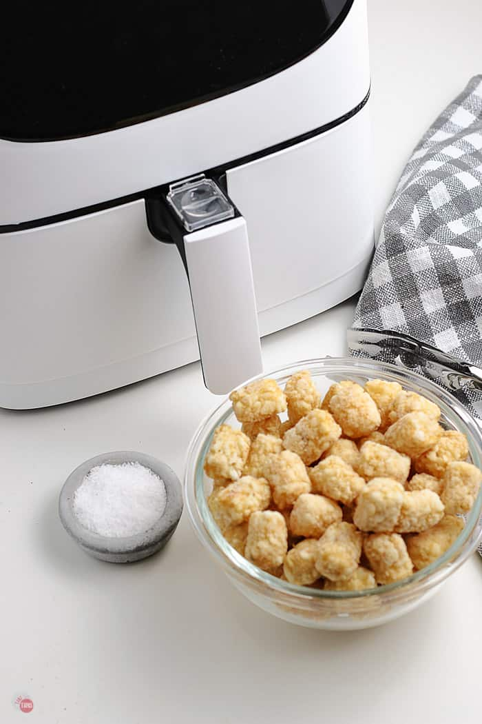 frozen tots in a bowl next to air fryer