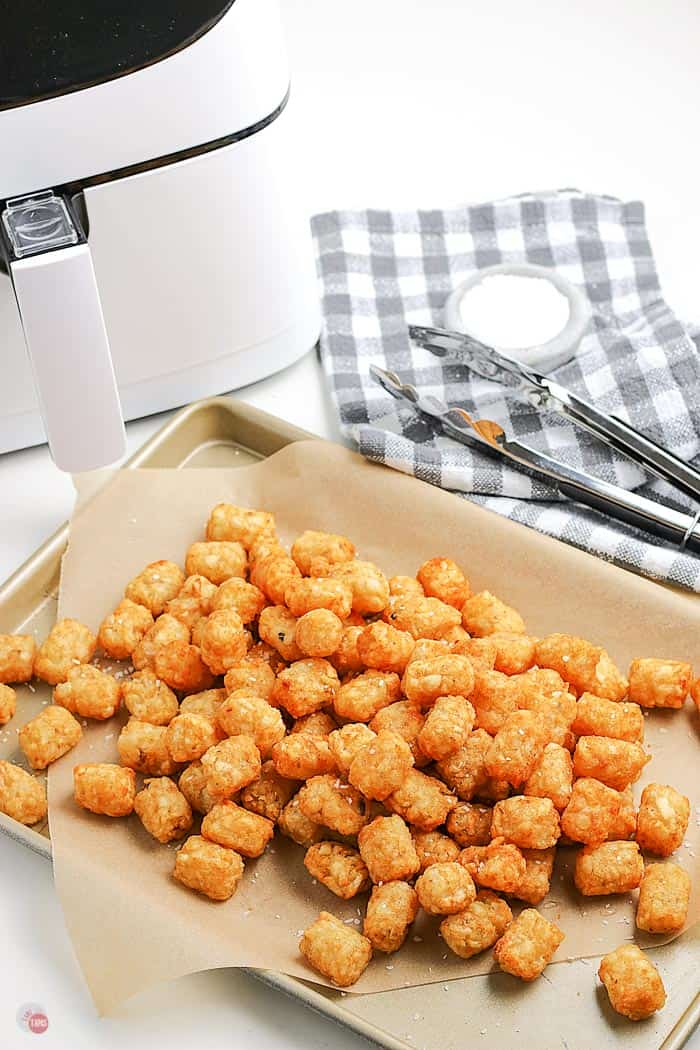 cooked tots on a platter with parchment paper