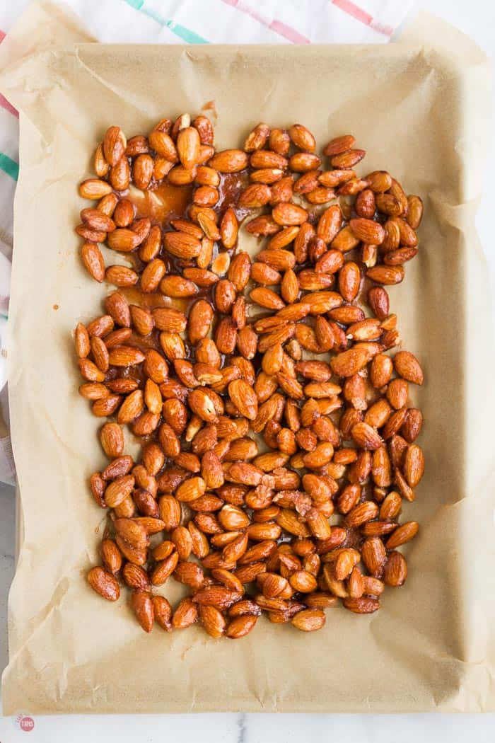 glazed almonds on a baking sheet with paper