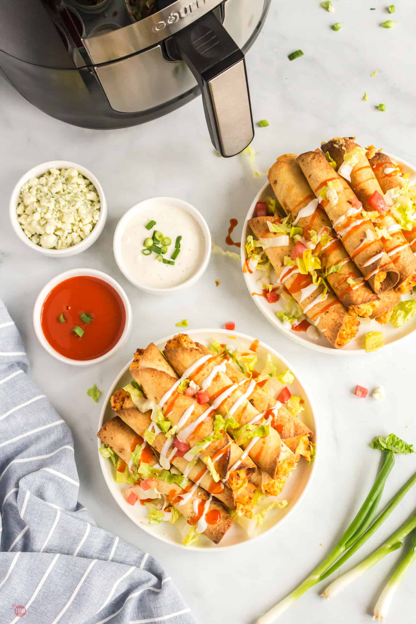 overhead picture of two plates of taquitos