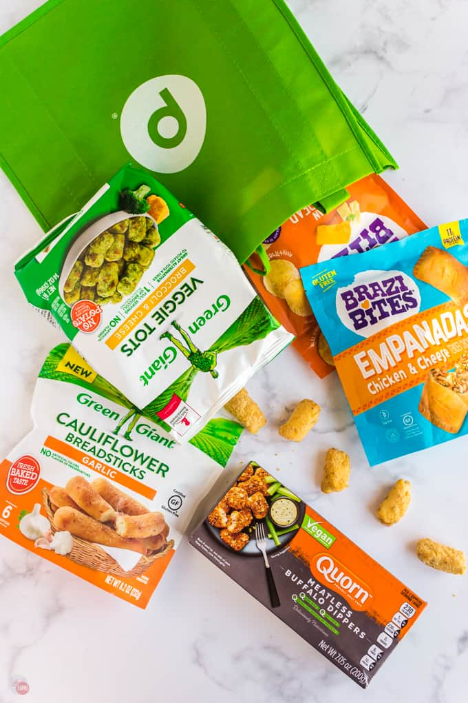 bags of food with green reusable shopping bag