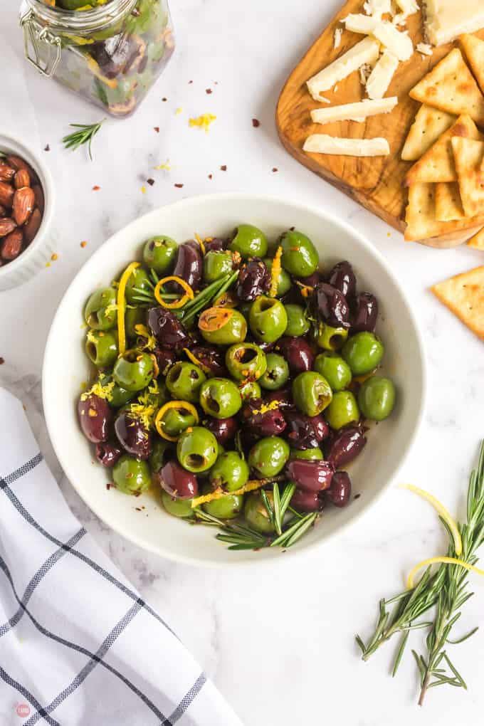 bowl of marinated olives with a cheese board