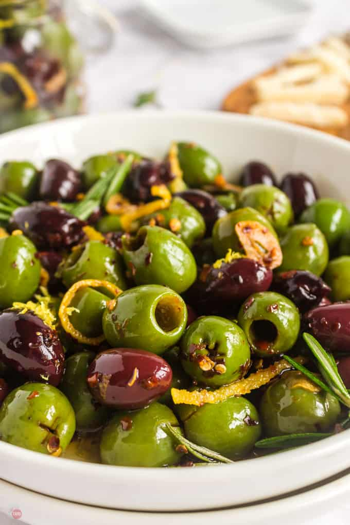 close up of olives in a white bowl