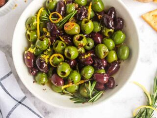 white bowl of olives and rosemary