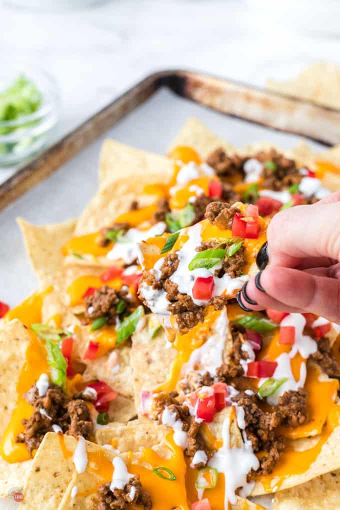 hand pulling nachos