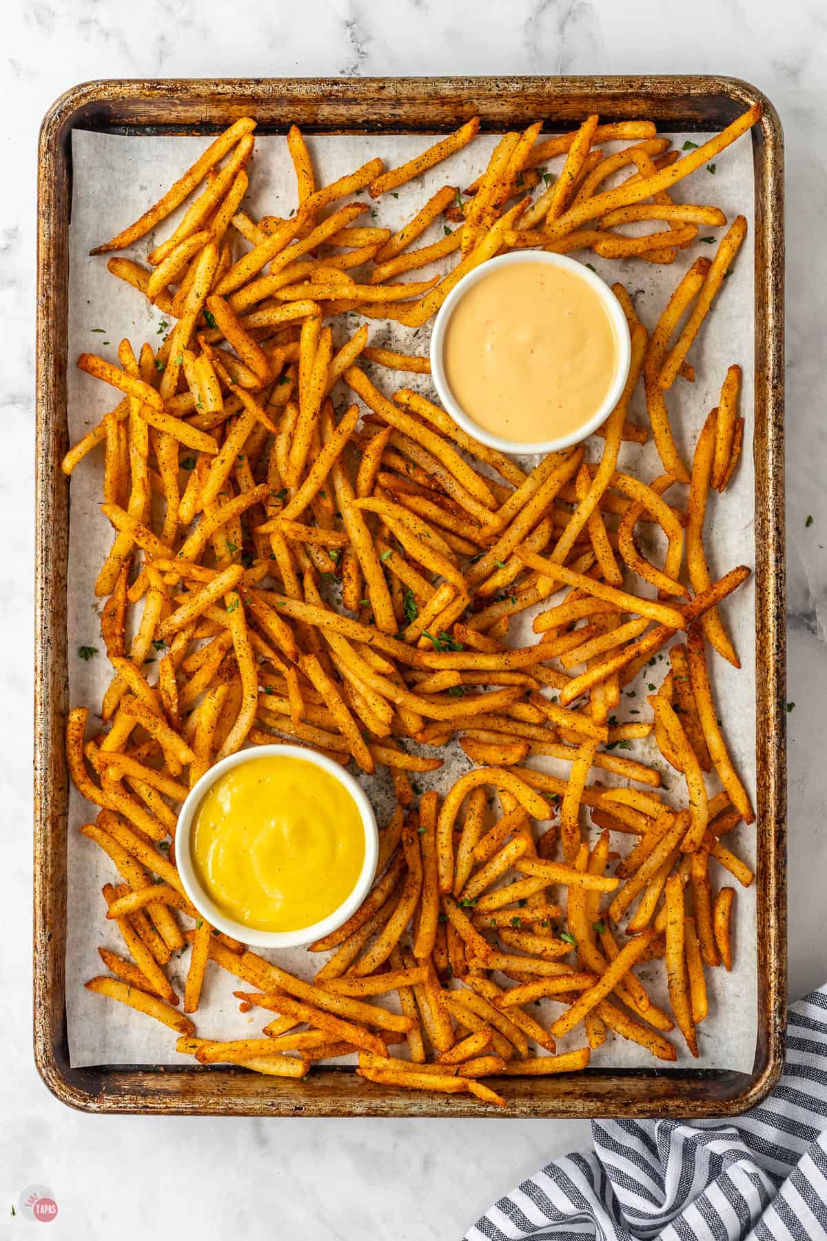 sheet pan of french fries with two bowls of dipping sauce