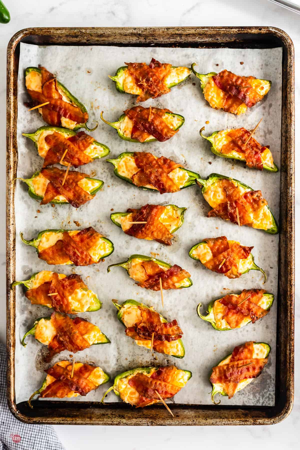 baked jalapeno poppers on a baking sheet