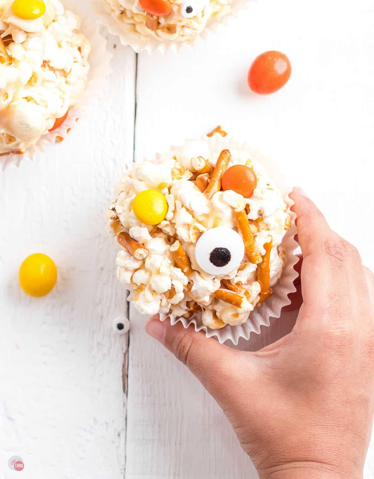 hand holding popcorn ball