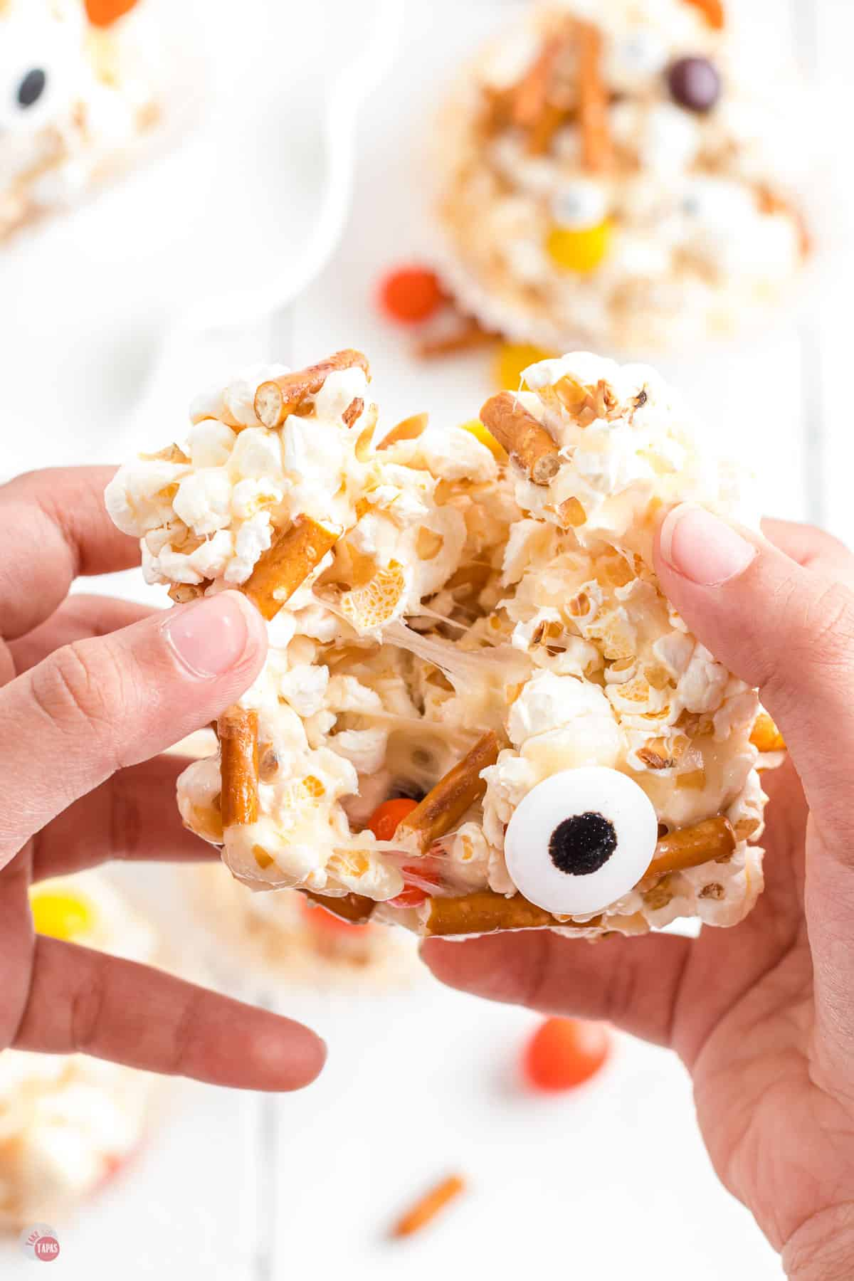 two hands pulling apart a popcorn ball