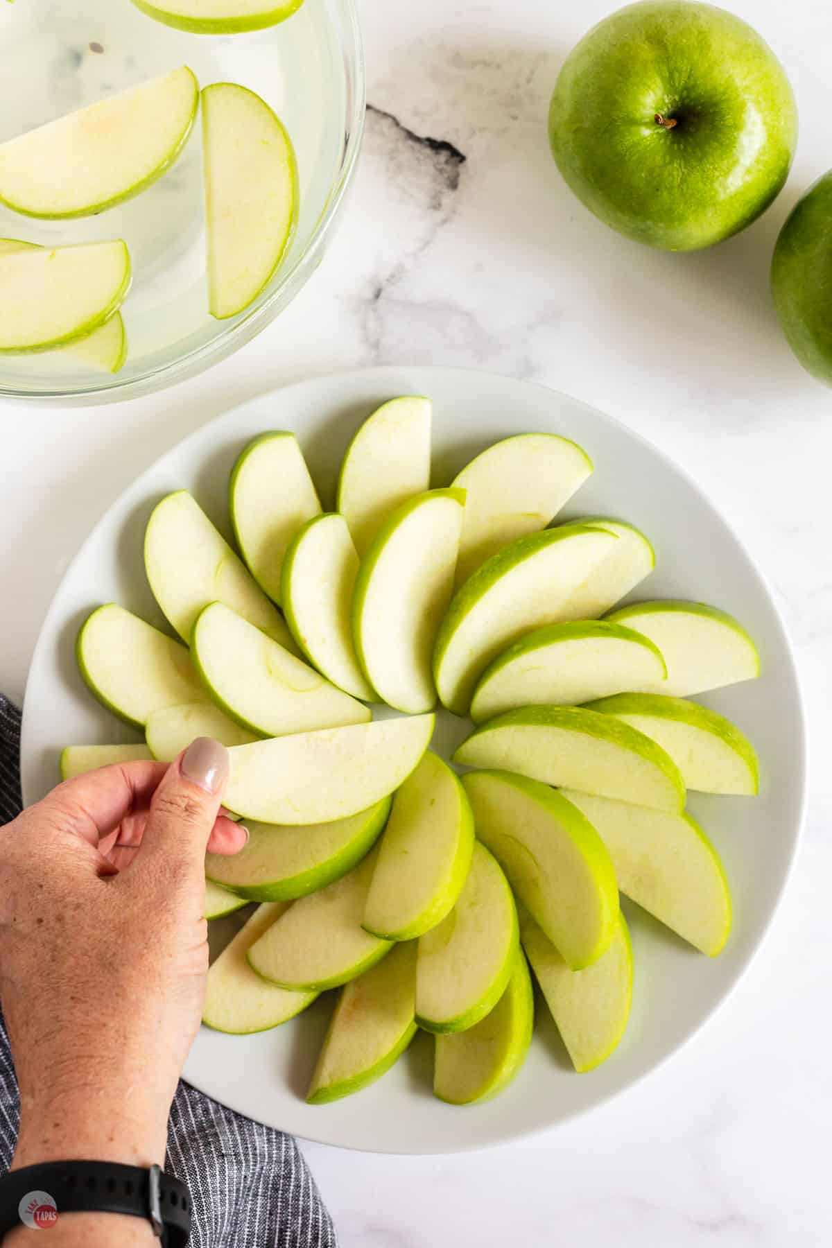 layering apple slices on white plate