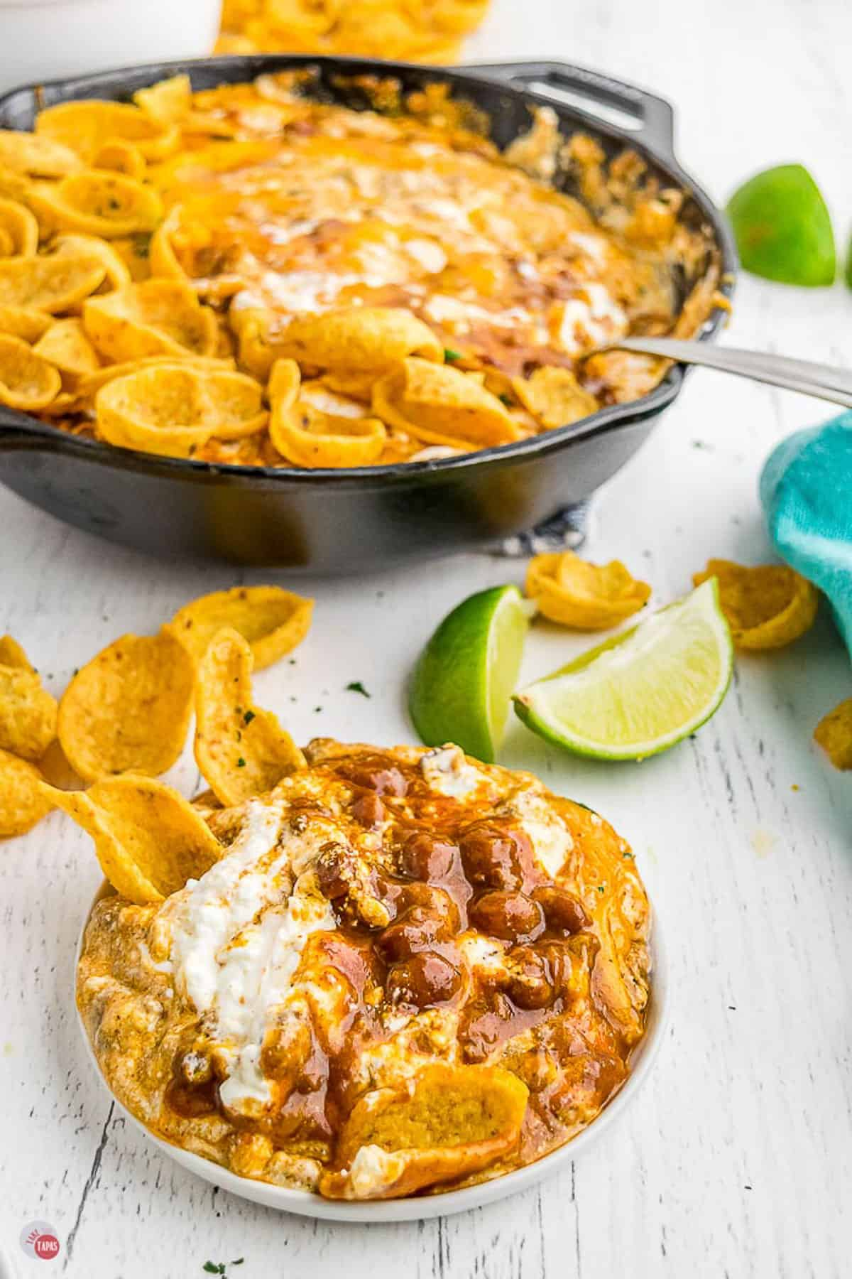 white bowl of easy frito pie dip in a white bowl with limes in the background