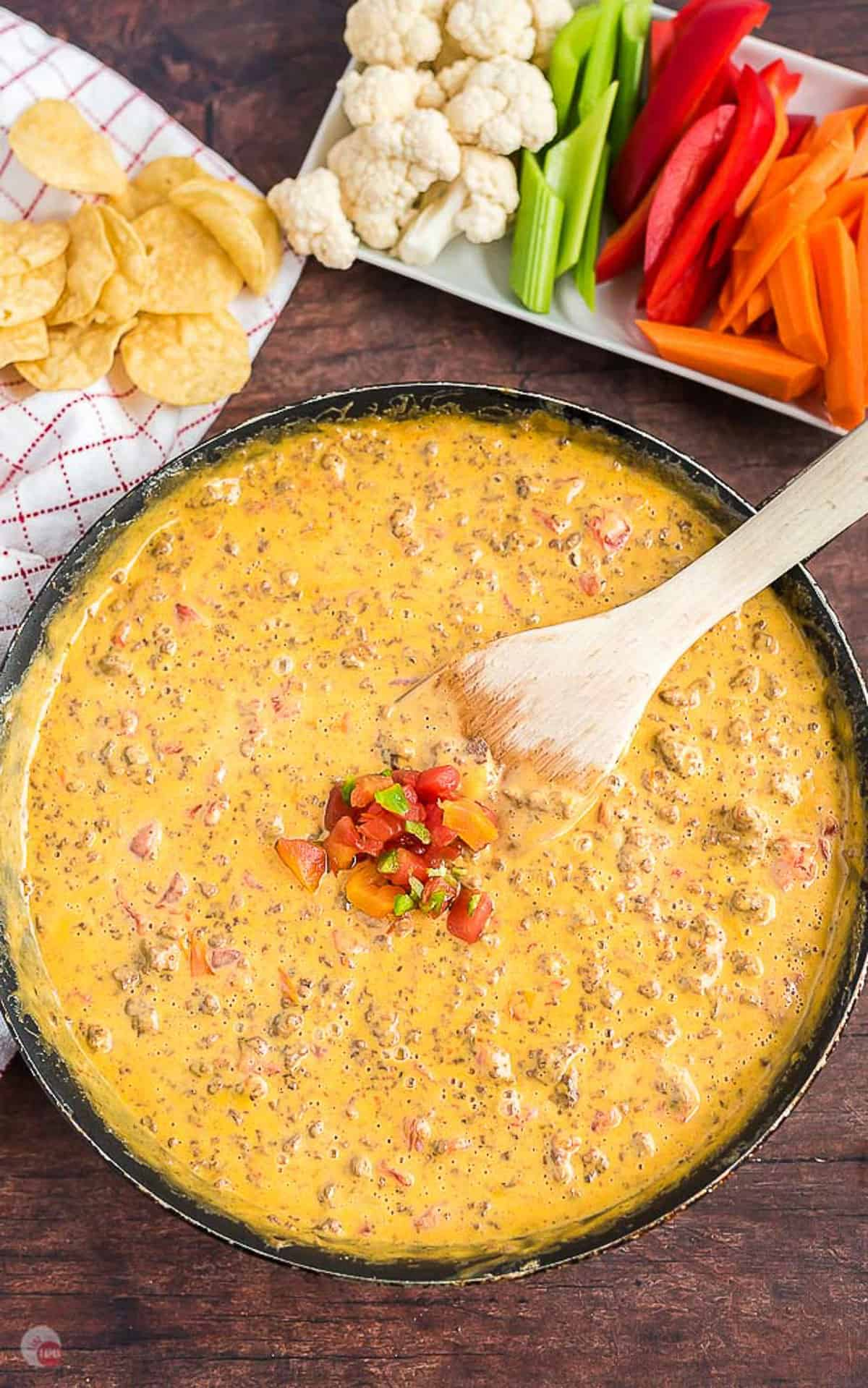 overhead picture of cheese dip topped with salsa in a pan with spatula in it and a napkin on the side and a tray of veggies